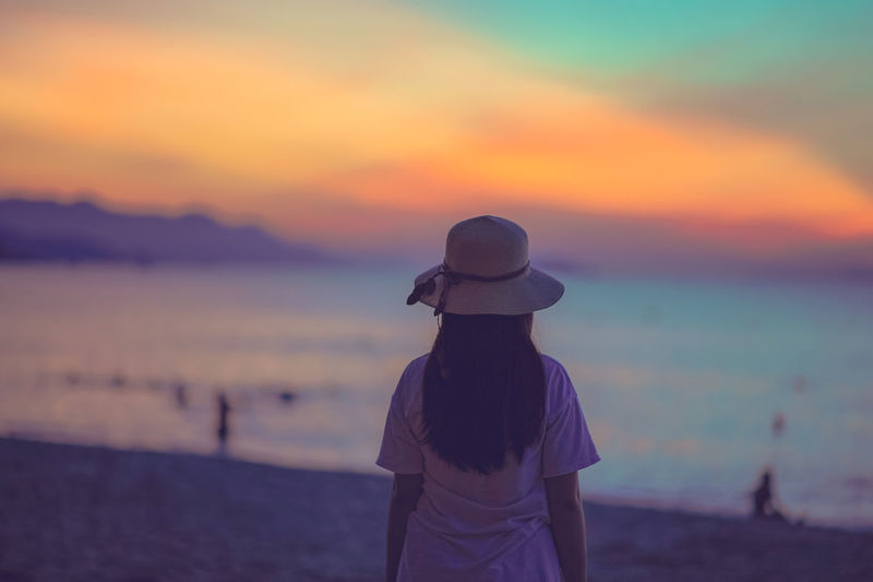 Rear view of woman standing at beach during sunset