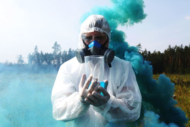 Portrait of scientist with liquid standing against blue smoke