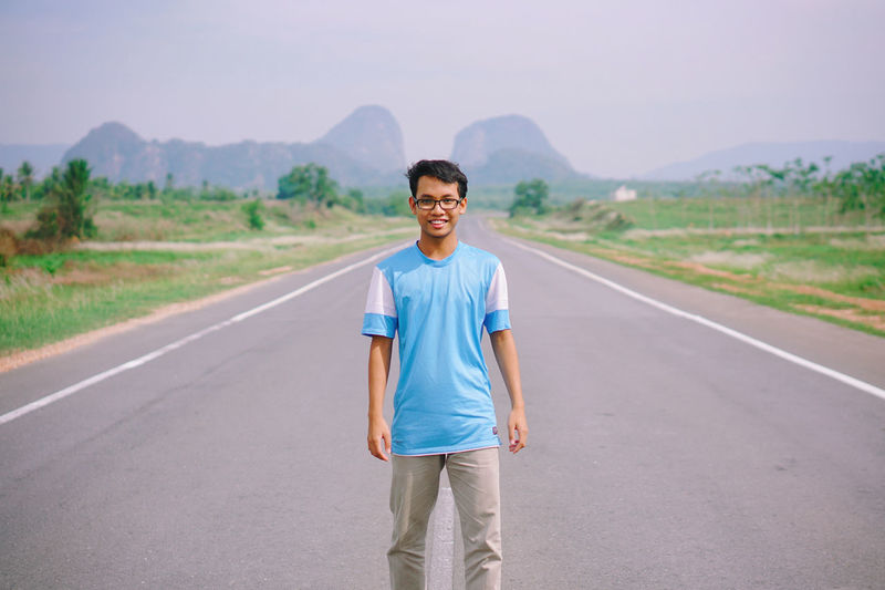 Portrait Of Man Standing On Road Against Clear Blue Sky