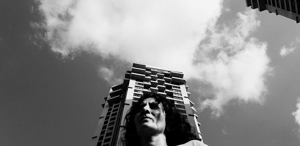Low angle portrait of man against building against sky