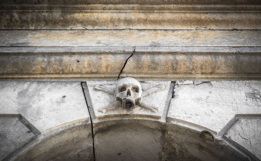 A stone skull placed near the entrance of a charnel house, in an Italian graveyard Ancient Antique Arch Architecture Art Bones Caronte Catholic Cemetery Charnel Church Cult Dead Death Entrance Europe Guardian Italy Relief Religion Sculpture Statue Symbol Symbolism Tomb