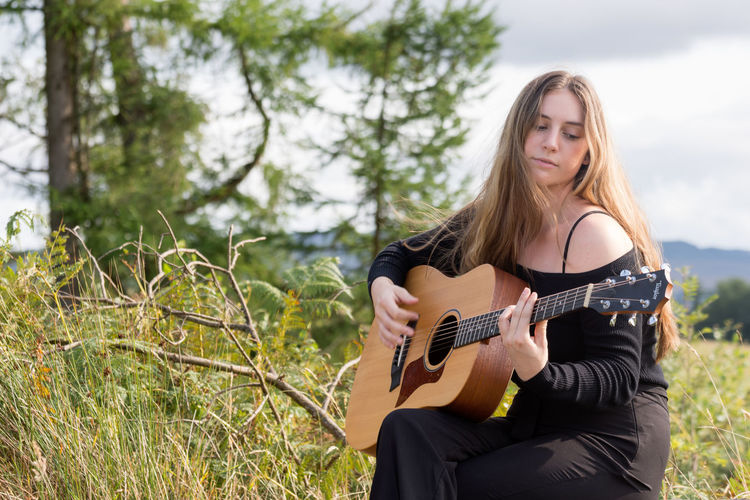 Singing a song in the Highlands Musical Instrument String Instrument Music Guitar Young Adult Playing One Person Long Hair Hair Musician Plant Plucking An Instrument Young Women Three Quarter Length Hairstyle Leisure Activity Arts Culture And Entertainment Sitting Tree Acoustic Guitar Skill  Beautiful Woman Outdoors
