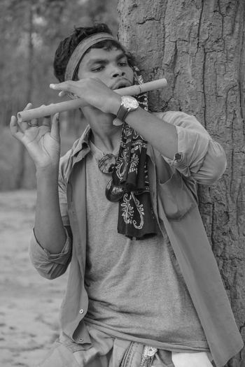 Man playing flute while standing against tree trunk