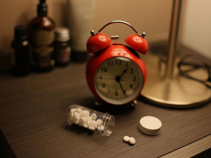 Close-up of pill bottle and alarm clock on table