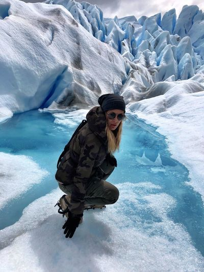 Portrait of mature woman crouching at glacier