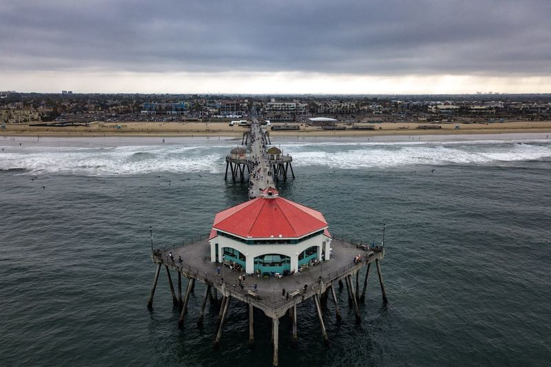 Aerial view of the Huntington Beach Pier toward the shore with a cloudy sky Dramatic Sky Huntington Beach Pier Surfers Paradise Wave Aerial View Architecture Beach Building Exterior Built Structure Cloud - Sky Coastal California Coastal Feature Day Drone Photography Idyllic Land Motion Nature Orange County Outdoors Scenics - Nature Sea Sky Water Wave
