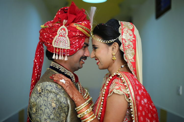 Side view of smiling bride and groom standing in room