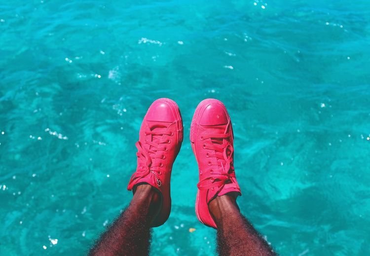 Low section of man wearing pink shoes poolside