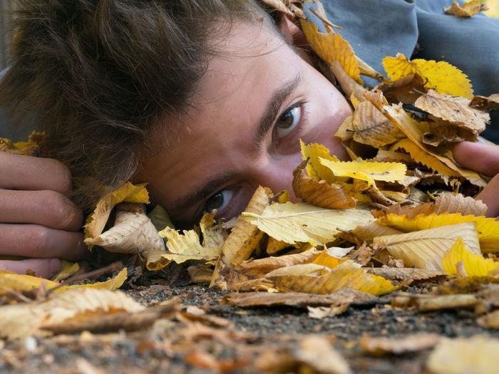 Teenager peeking from behind dry leaves
