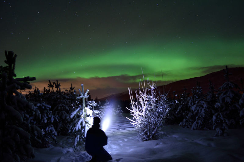 Full length of a man on snow covered landscape at night