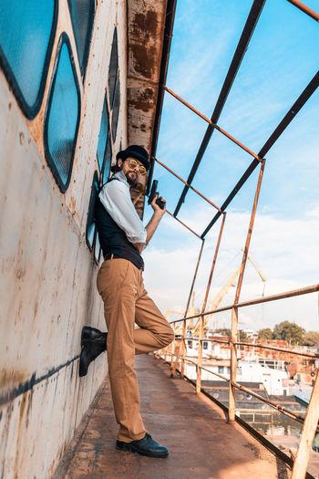 Man standing on bridge against sky