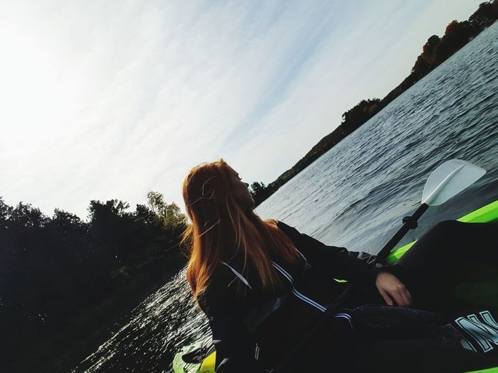 Tilt image of woman looking away while sitting in boat on river against sky