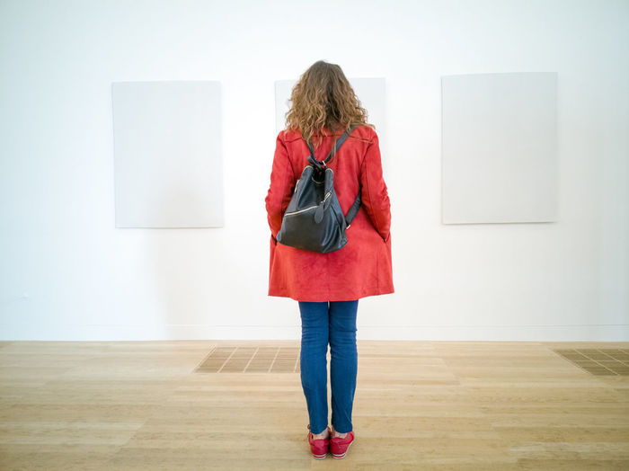 White wall Indoors  Woman Girl Red Colour White Wall Exhibition Gallery Looking At The Wall Coloured Clothes Standing Still Red Coat Indoor Rier View Empty Space Minimal