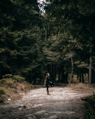 Side View Of Woman Standing On Road In Forest