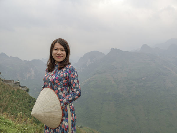 Young Vietnamese women facing and pose for camera with stunning view of the Nho Que river surrounded by mountains from the Ma Pi Leng pass in northern Vietnam Mountain Cloudy Green Color Meo Vac Vietnam Vietnamese Ao Dai Beauty In Nature Casual Clothing Hairstyle Idyllic Landscape Leisure Activity Lifestyles Looking At Camera Mountain Mountain Range Nature Non-urban Scene One Person Outdoors People Portrait Pose Real People Scenics - Nature Sky Smiling Standing Sunrise Traditional Dress Valley Women Young Adult