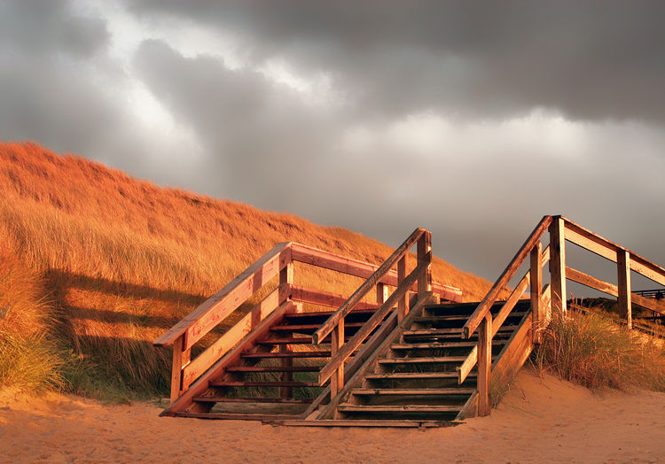 Staircase on landscape against sky