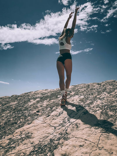 Full length of young woman with arms raised standing on mountain against sky during sunny day