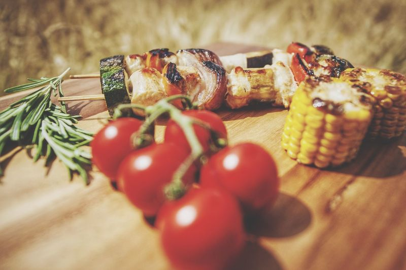 Close-up of tomatoes and kebab and sweetcorns on table