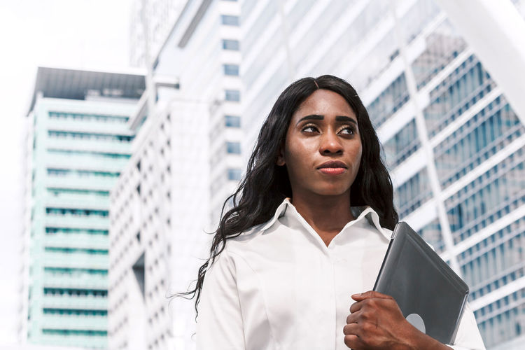 African woman holding laptop on office building background Adult Architecture Building Building Exterior Built Structure Business Business Person Businesswoman City Contemplation Corporate Business Financial District  Front View Low Angle View Office Office Building Exterior One Person Portrait Skyscraper Standing Women Young Adult