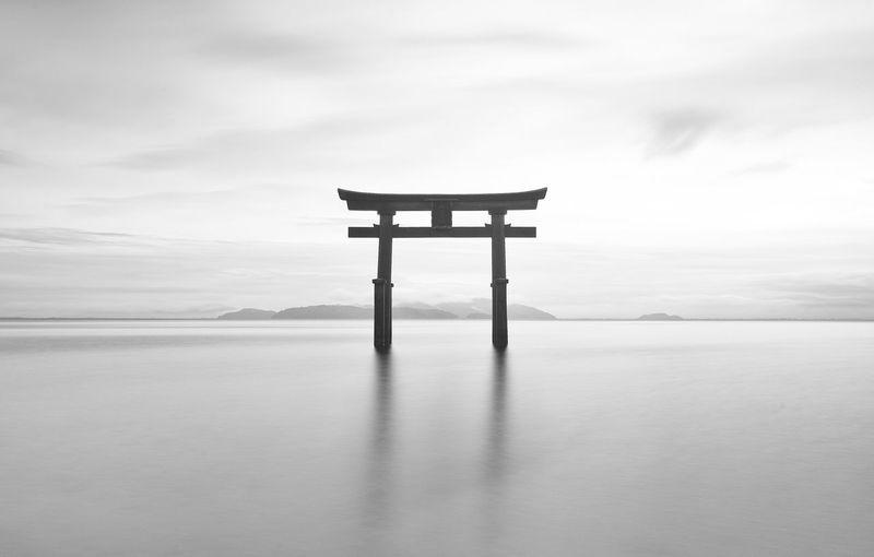 Torii gate in sea against sky