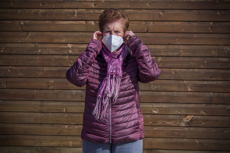 Senior woman with medical mask on face in prevention of coronavirus with wall background
