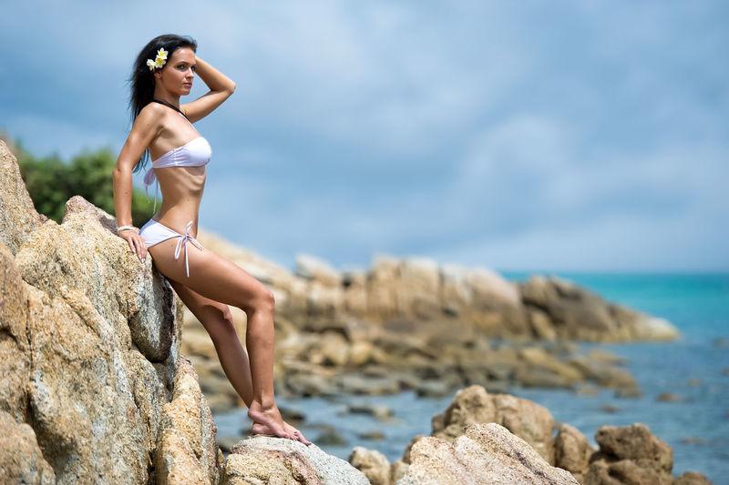 Full length of young woman in bikini leaning on rock by sea