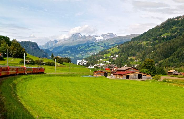 Glacierexpress Train Alps Green Grass Mountain Beauty In Nature Landscape Field Sky Nature Green Scenics Built Structure House Grass Building Exterior Tranquil Scene Idyllic No People Architecture Tranquility Mountain Range Outdoors Green Color