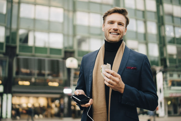 Smiling man holding camera while standing against mobile phone