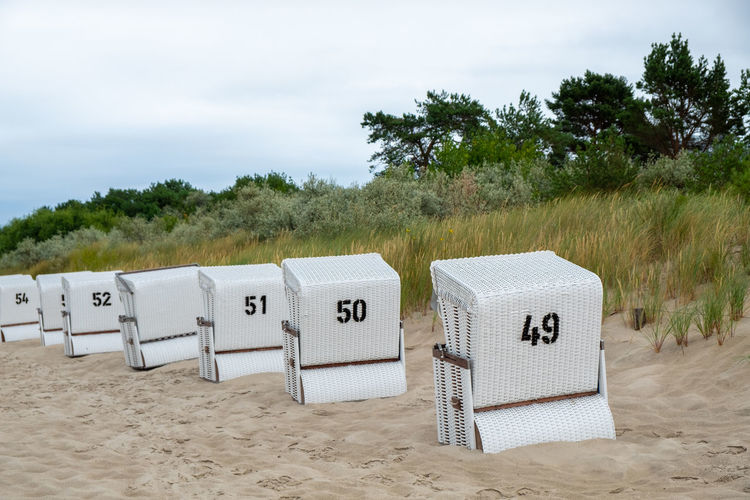 Hooded chairs on sand at beach against sky