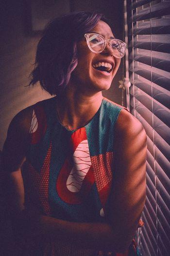 Laughing woman looking through window