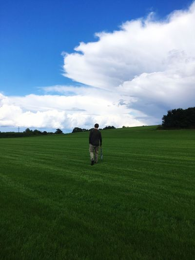 Rear view of man walking on grassy field against cloudy sky