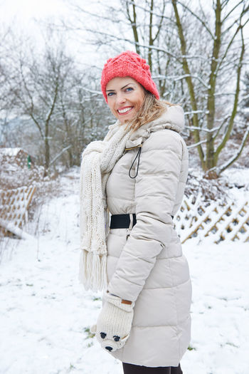 portrait of woman standing on snow covered tree Active Beautiful Woman Cap Cheerfulness Clothing Cold Temperature Fun Garden Happy Holiday Knit Hat Laughing Leisure Leisure Activity Lifestyle Lifestyles Looking At Camera Nature One Person Outdoors Outside People Portrait Real People Scarf Ski Holiday Ski Trip Smile Smiling Snow Standing Stroll Tree Walk Warm Clothing Winter Winter Clothing Winter Holiday Woman Women Young Adult Young Women