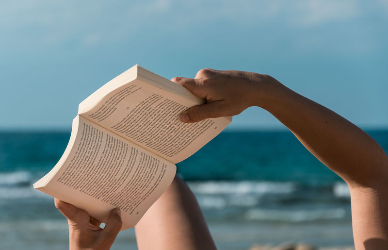 Low angle view of hand holding a book at beach against sky