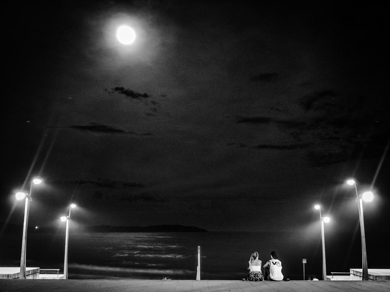 night, illuminated, sky, real people, sea, lighting equipment, men, leisure activity, street light, water, outdoors, moon, togetherness, beach, lifestyles, cloud - sky, women, nature, scenics, horizon over water, standing, nautical vessel, beauty in nature, people