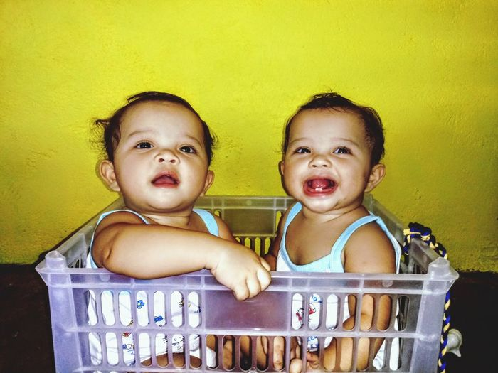 Close-up of smiling twin sisters in basket against yellow wall