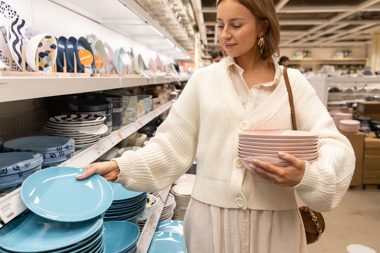 Woman customer choosing and buying clay dishes plates, dinner utensil in houseware store