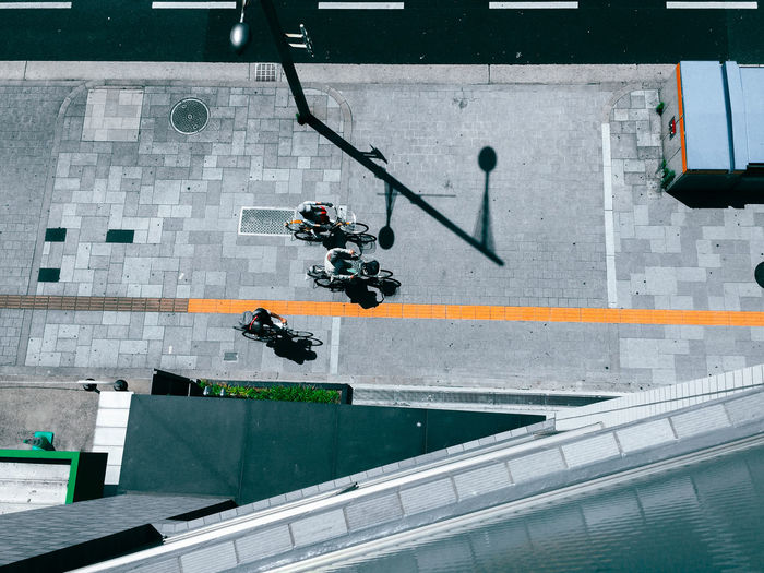 High angle view of men riding bicycle on sidewalk during sunny day