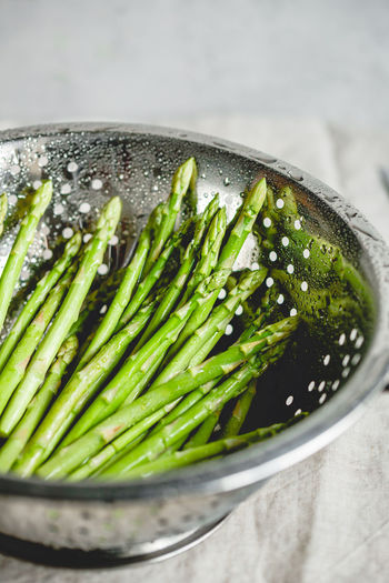 Asparagus in colander on table
