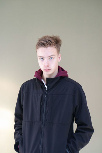 Looking At Camera Portrait One Person Front View Studio Shot Indoors  Young Adult Young Men Standing Gray Background Gray Colored Background Casual Clothing Waist Up Real People Lifestyles Teenager Males  Adolescence  Teenager Boy Confidence  Confident  Skin Hoodie Hoodieseason