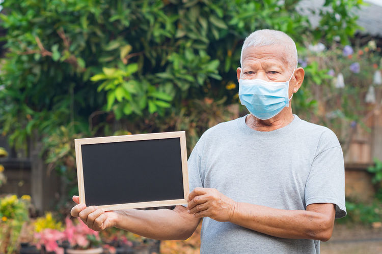 Portrait of an elderly man wearing a face mask and holding a blackboard standing in a garden