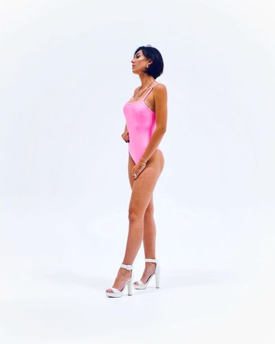 Woman looking away while standing against white background