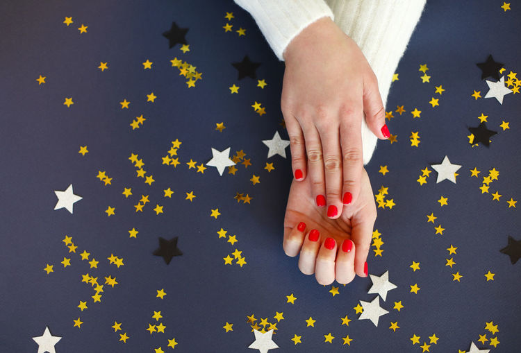 Cropped hands of woman with star shape on colored background