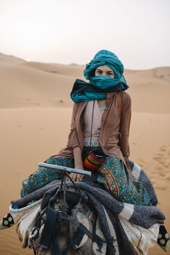 Portrait of woman wearing turban while sitting on camel at desert
