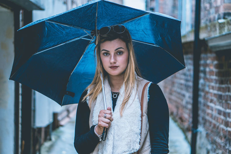 Portrait Of Young Woman With Umbrella Standing On Street During Monsoon
