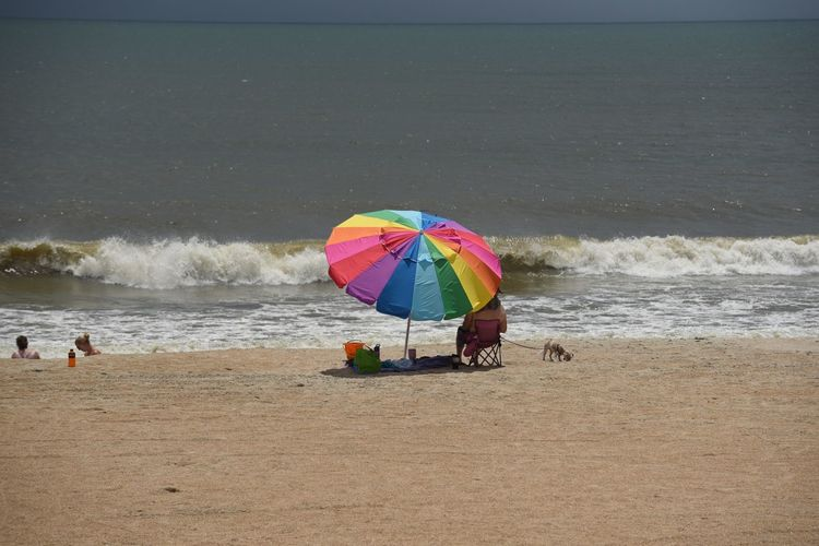 Beach Land Sea Water Umbrella Sand Beauty In Nature Scenics - Nature Protection Real People Nature Motion Wave Holiday Parasol Day Vacations Sky Sport Horizon Over Water