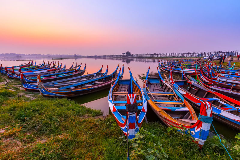 Fishing boats moored at riverbank against sky during sunset