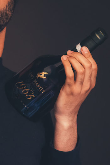 A young man carrying a champagne 1965 Champagne Remy Martin Alcohol Bad Habit Beard Beauty Bottle Class Close-up Finger Hand High Angle View Holding Human Hand Indoors  Lifestyles Men One Person Real People Wine