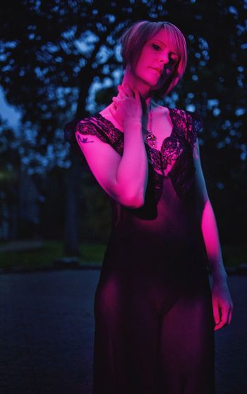 Portrait of seductive woman standing against trees at dusk