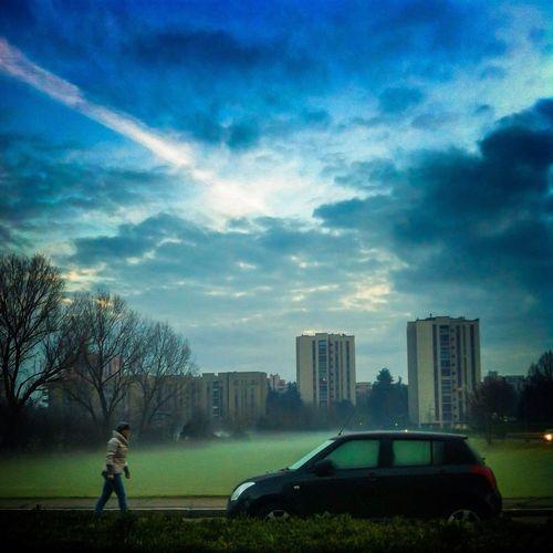People walking on city street against cloudy sky