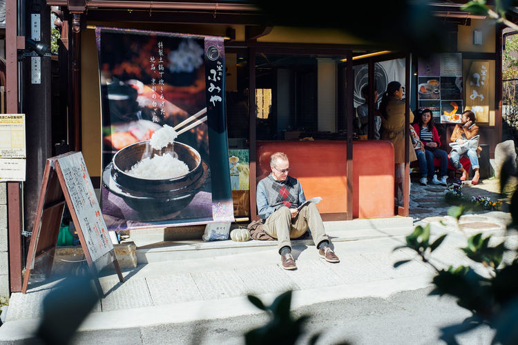 Man sitting at market in city
